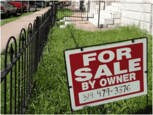 """For Sale by Owner"" Sign in Front of a House"